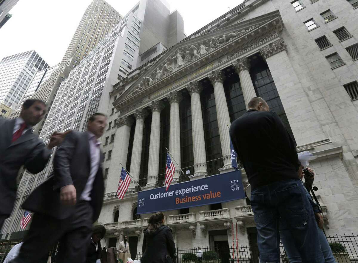 People pass the New York Stock Exchange in New York.