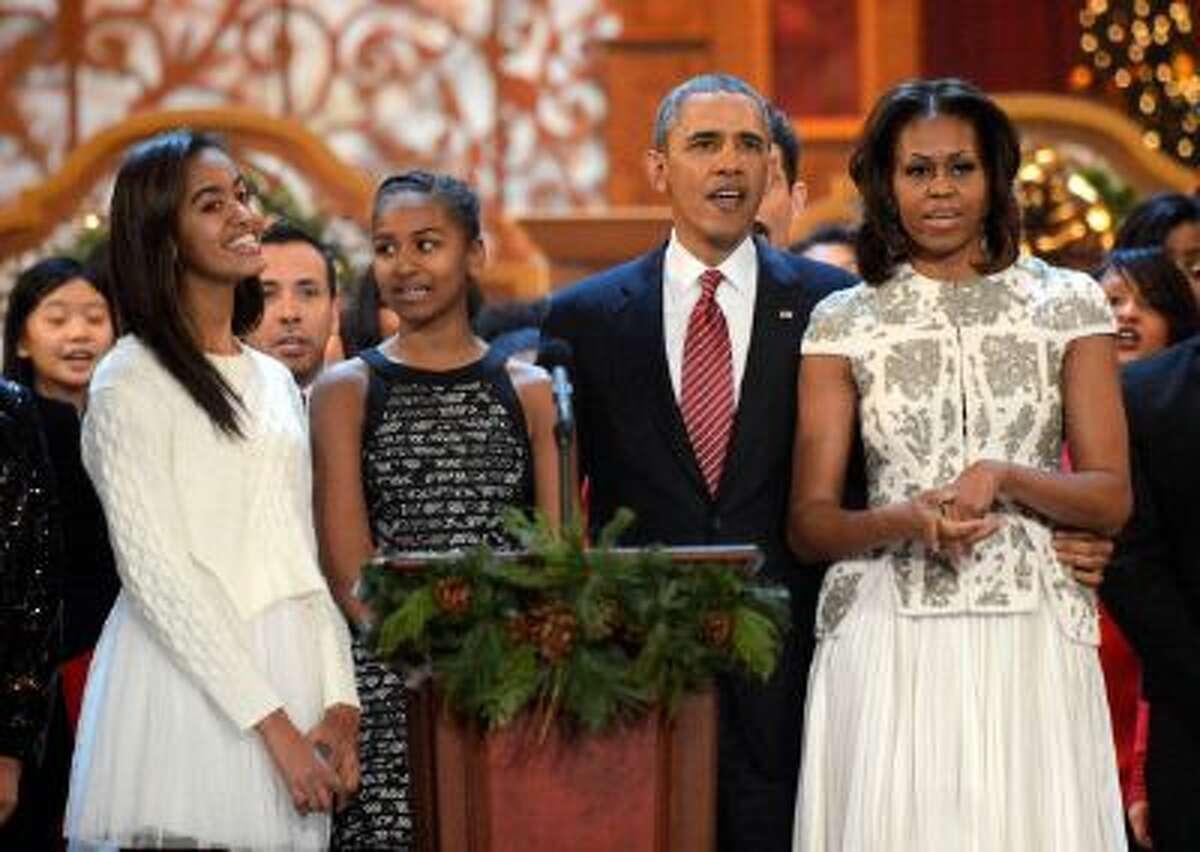 Malia Obama, Sasha Obama, President Barack Obama, and First Lady Michelle Obama onstage at TNT Christmas in Washington 2013 at the National Building Museum on Dec. 15, 2013 in Washington, DC.