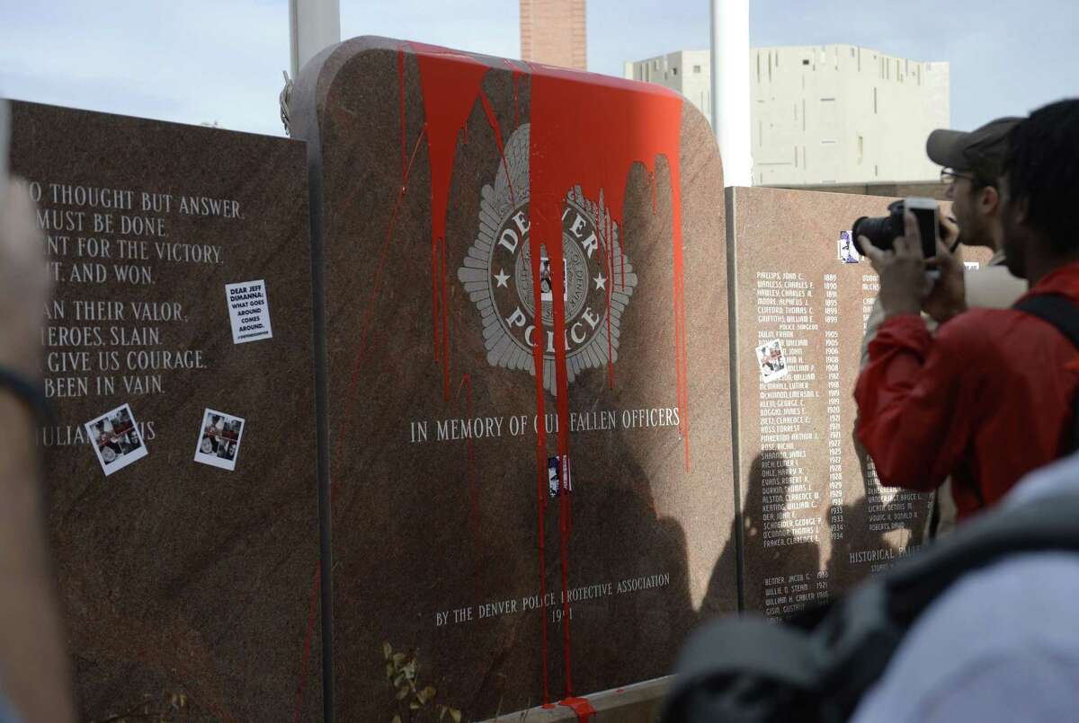 In this photograph taken Saturday, Feb. 14, 2015, protesters take pictures of red paint that was thrown on the memorial to fallen police officers located outside Denver Police headquarters in Denver. More than 100 protesters marched in the streets of Denver to call attention to several recent on-duty police shootings. Protesters defaced the memorial during the march and a decision by Denver Police Chief Robert White to not approach the protesters has triggered counter protests by officers and their supporters. (AP Photo/The Denver Post, Brent Lewis) MAGS OUT; TV OUT; INTERNET OUT; NO SALES; NEW YORK POST OUT; NEW YORK DAILY NEWS OUT