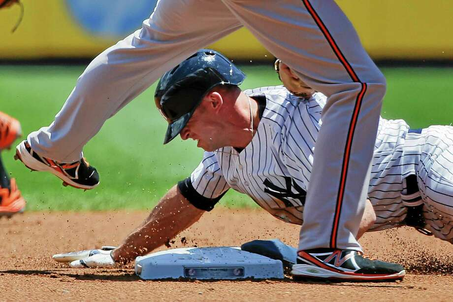 Yankees left fielder Brett Gardner is tagged out trying to steal second base by Baltimore Orioles shortstop J.J. Hardy in the first inning of Saturday's game in New York. Photo: Julie Jacobson — The Associated Press  / AP