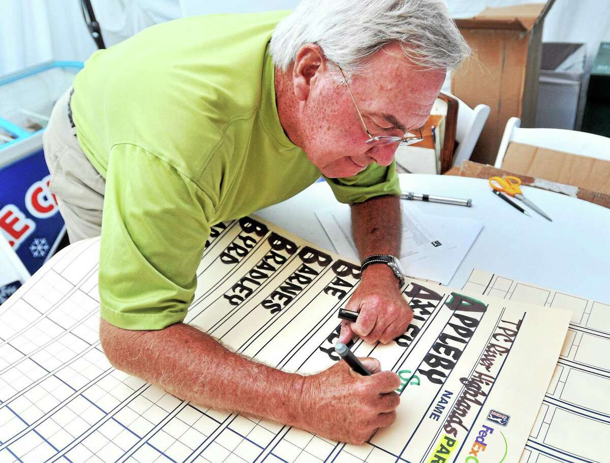 Calligrapher Dave Koenig writes the 77 players' names on the scoreboard Friday in preparation for the third round of the Travelers Championship in Cromwell.