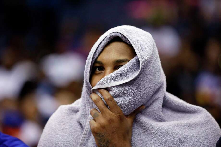 New York Knicks forward Carmelo Anthony wears a towel over his head on the bench during last Friday's preseason game against the Wizards in Washington. Photo: Alex Brandon — The Associated Press  / AP
