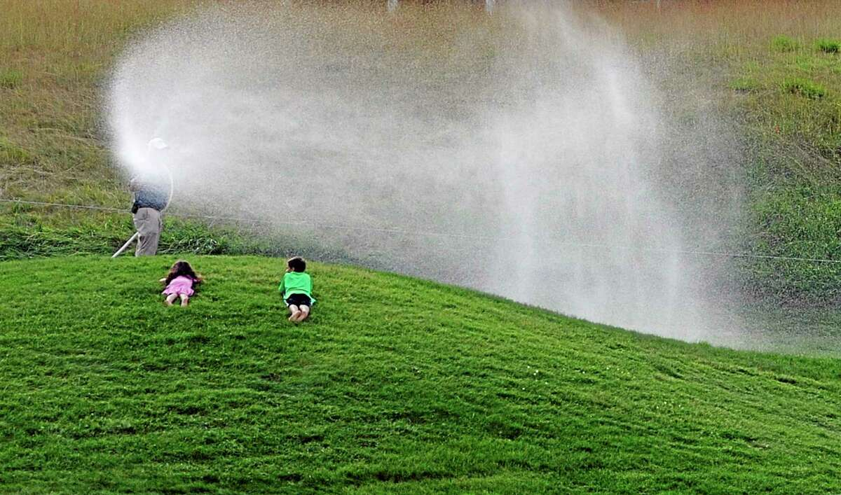 Two children watch a greenskeeper water the first green during the third round of the Travelers Championship on Saturday in Cromwell.