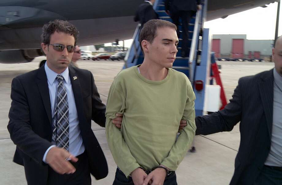 FILE - In this June 18, 2012 file photo provided by Montreal Police, Luka Rocco Magnotta is taken by police from a Canadian military plane to a waiting van in Mirabel, Quebec. Magnotta dropped his appeal Wednesday, Feb. 18, 2015 of a life sentence for killing and dismembering his Chinese lover and mailing his body parts to schools and political parties. Magnotta, 32, was sentenced to life in prison last December in the slaying and dismemberment of Jun Lin, a 33-year-old Chinese engineering student who had been living in Canada since 2011.  (AP Photo/Montreal Police) Photo: AP / Montreal Police via The Canadian Press