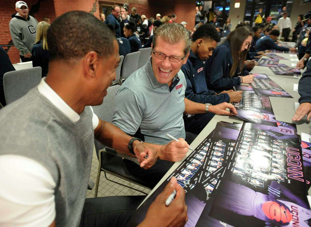 UConn women's basketball coach Geno Auriemma, right, shares a light moment with men's coach Kevin Ollie during an autograph session Friday at First Night in Storrs.