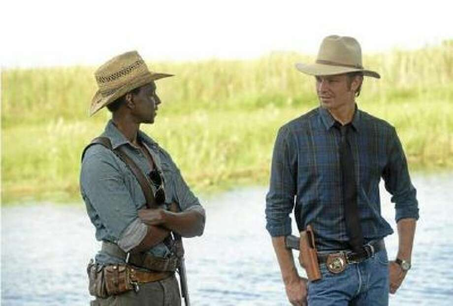 JUSTIFIED -- A Murder of Crowes -- Episode 501 (Airs Tuesday, January 7, 10:00 pm e/p) -- Pictured: (L-R) Edi Gathegi as Jean Baptiste, Timothy Olyphant as Deputy U.S. Marshal Raylan Givens.
