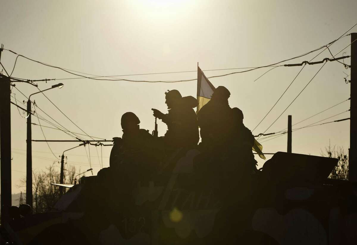 Ukrainian troops ride on an armored vehicle outside Artemivsk, Ukraine, while withdrawing from Debaltseve, Wednesday, Feb. 18, 2015. After weeks of relentless fighting, the embattled Ukrainian rail hub of Debaltseve fell Wednesday to Russia-backed separatists, who hoisted a flag in triumph over the town. The Ukrainian president confirmed that he had ordered troops to pull out and the rebels reported taking hundreds of soldiers captive.(AP Photo/Vadim Ghirda)