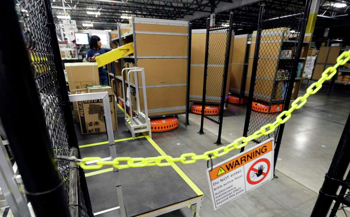 In this Feb. 13, 2015, file photo, a sign warns employees to stay away from an area where KIVA robotic transport units are in motion, during a media tour of the new Amazon fulfillment center in DuPont, Wash. The center is one of 50 around the country and three in the Puget Sound area that process and ship Amazon customer orders using a mix of robotic technology and human employees.