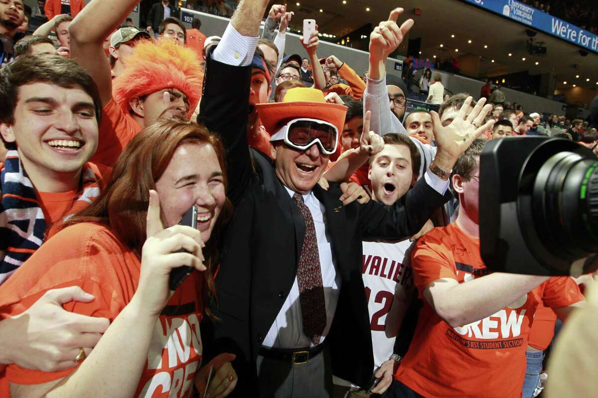 Sportcaster Dick Vitale, center, poses with Virginia fans before a game against Louisville on Feb. 7 in Charlottesville, Va.