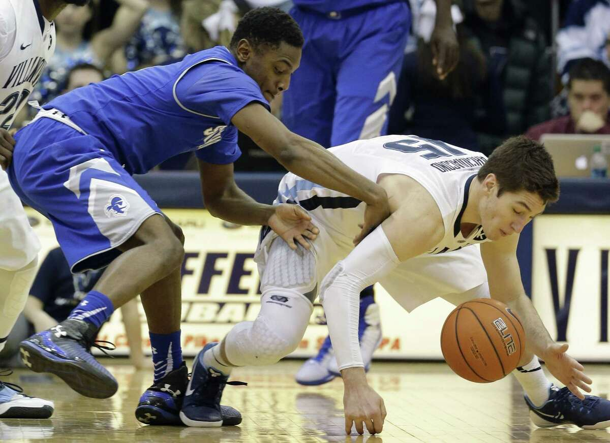 Villanova's Ryan Arcidiacono, right, dives for a loose ball against Seton Hall's Sterling Gibbs during the second half of Monday's game in Villanova, Pa.