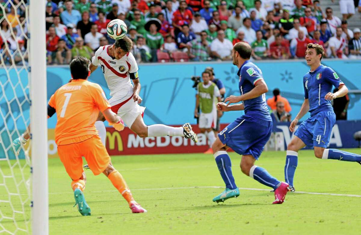 Costa Rica's Bryan Ruiz heads the ball to score his side's first goal over Italy goalkeeper Gianluigi Buffon during the group D World Cup match on Friday at the Arena Pernambuco in Recife, Brazil.