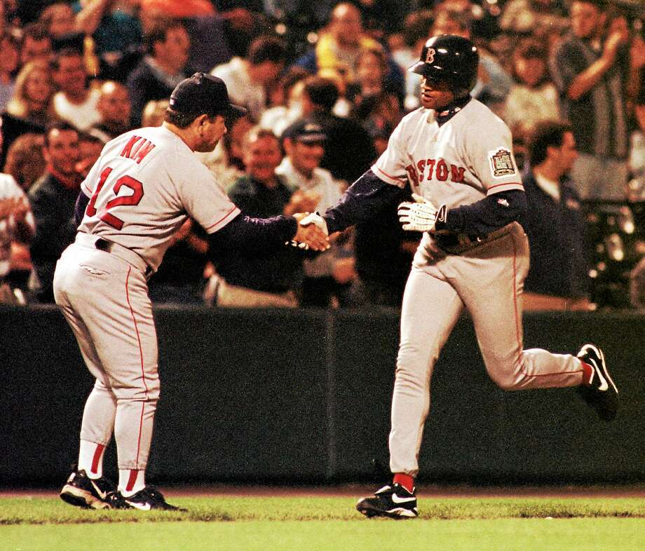 Boston's Damon Buford is congratulated by third base coach Wendell Kim after Buford hit a grand slam in the ninth inning of the Red Sox's 8-0 victory over the Orioles in Baltimore. Photo: Dave Hammond — The Associated Press File Photo  / AP1999
