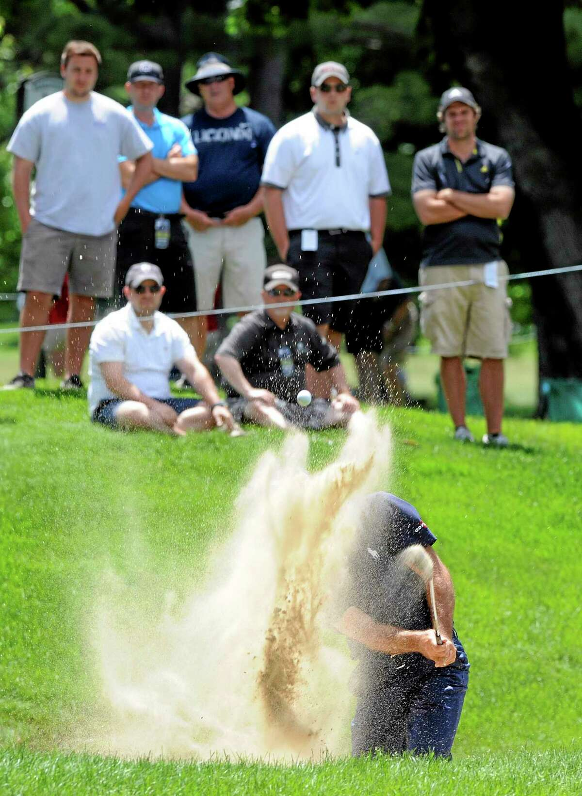 The crowd looks on as Jonathan Byrd hits out of a greenside bunker on the seventh hole during the second round of the Travelers Championship on Friday in Cromwell. Byrd aced the par-3 11th.