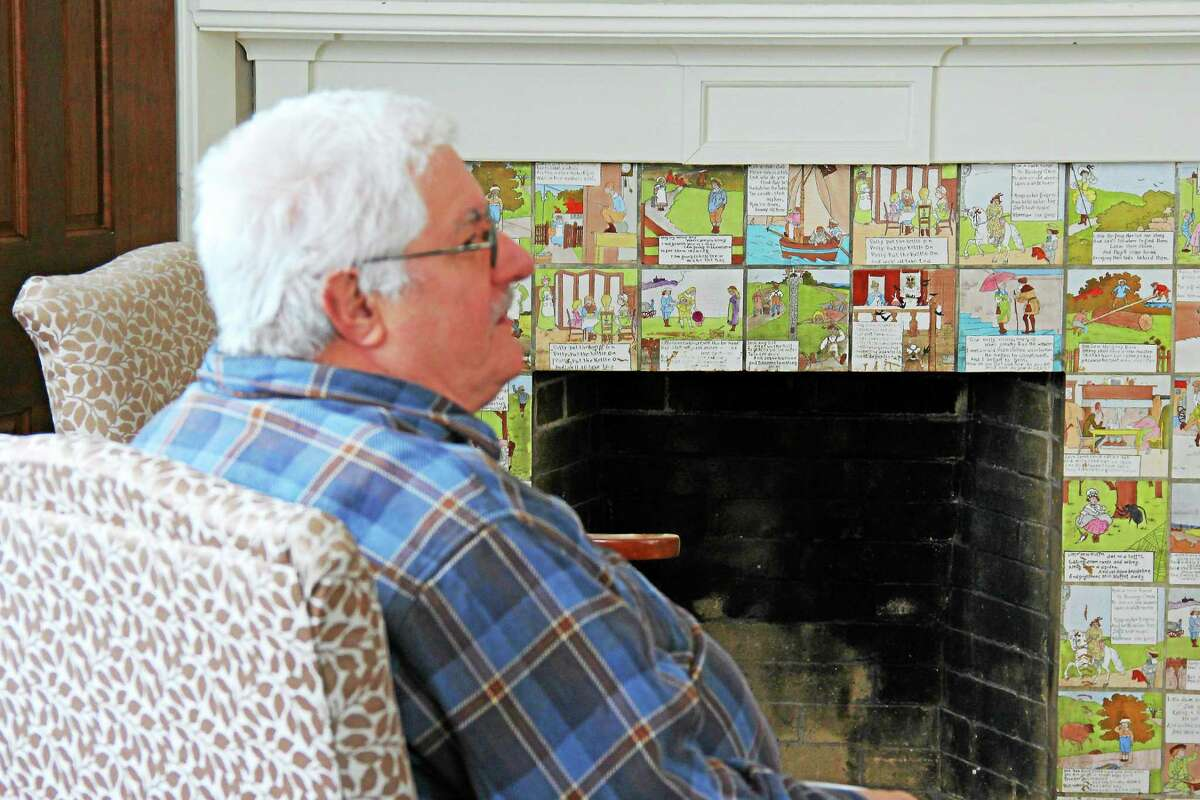 Resident Jim Misenti sits before an original fireplace with nursery rhyme tiles from the early 1930s. It was preserved, along with a fireplace and a 15-by-5-foot mural made by artist Albert McCutcheon in 1935, which covers an entire wall in the former principalís office.