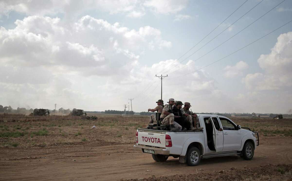 In this June 10, 2015 photo, Palestinian Hamas gunmen ride on the back of a pick-up truck as they patrol the border with Israel near the southern Gaza Strip town of Khan Younis, as Israeli military bulldozers are seen in the background.