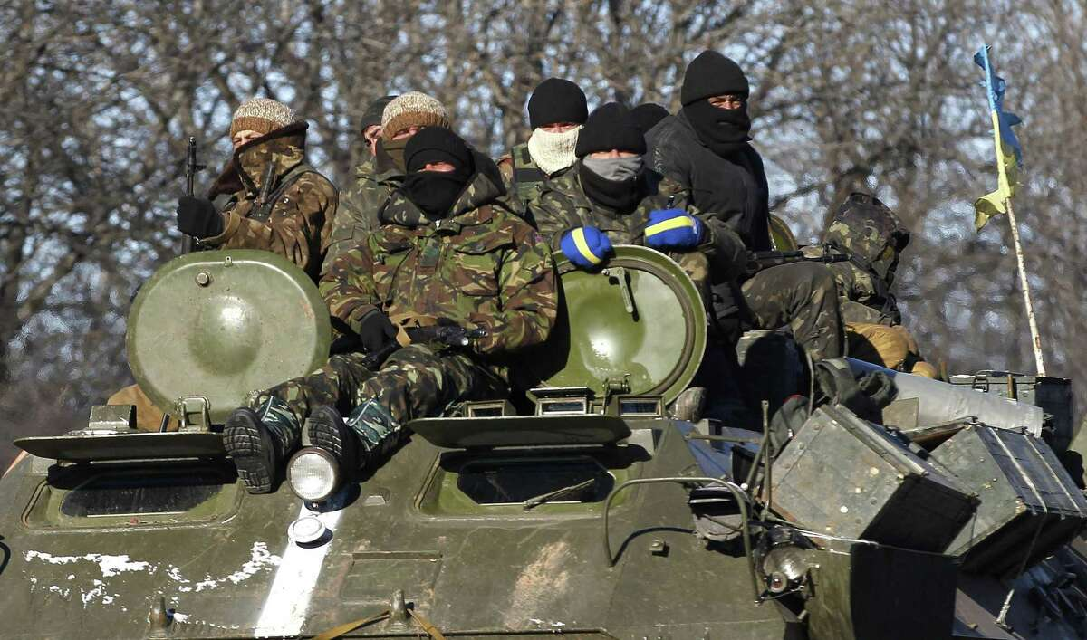 Ukrainian government soldiers sit on top of their armored vehicle driving on a road stretching away from the town of Artemivsk, Ukraine, towards Debaltseve, Tuesday, Feb. 17, 2015.