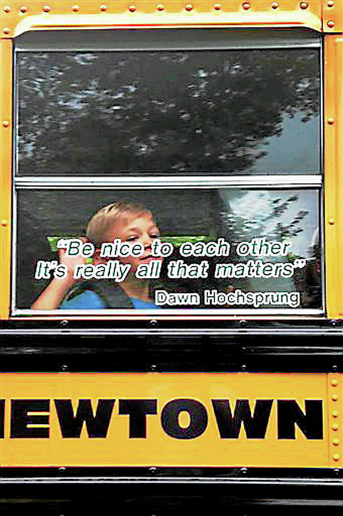 AP10ThingsToSee - In this photo provided by Craig Hoekenga, his son Trey Hoekenga, a kindergarten student at Sandy Hook Elementary School, waves from the school bus on the first day of school Tuesday, Aug. 27, 2013, in Newtown, Conn. On the bus window is a quote by the late principal, Dawn Hochsprung: