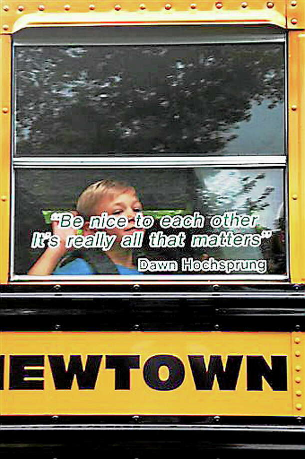 """AP10ThingsToSee - In this photo provided by Craig Hoekenga, his son Trey Hoekenga, a kindergarten student at Sandy Hook Elementary School, waves from the school bus on the first day of school Tuesday, Aug. 27, 2013, in Newtown, Conn. On the bus window is a quote by the late principal, Dawn Hochsprung: """"Be nice to each other. It's really all that matters."""" Hochsprung was among 26 people killed at the school by gunman Adam Lanza on Friday, Dec. 14, 2012. Students from the school are being bused to the neighboring town of Monroe where a former middle school was renovated for them after the shootings. (AP Photo/Craig Hoekenga, File) Photo: AP / Craig Hoekenga"""