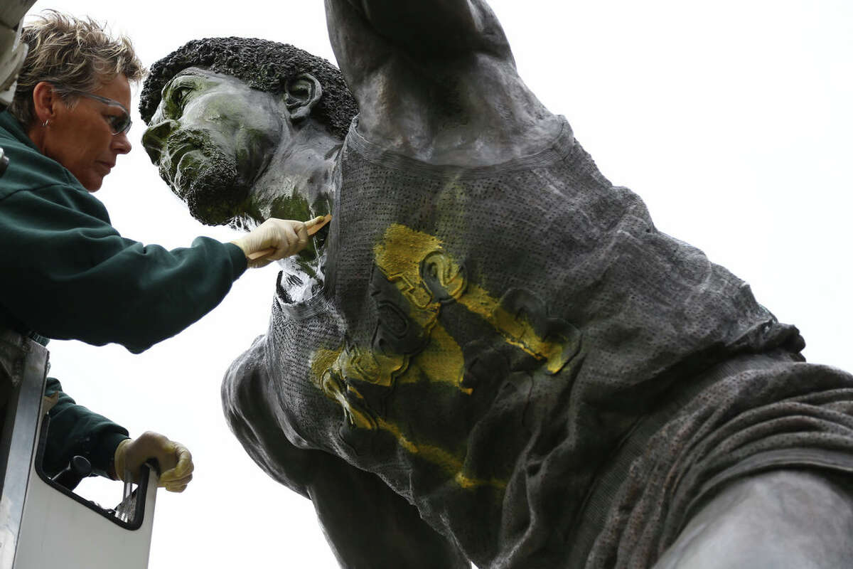 """Tracy Harris cleans a statue of Earvin """"Magic"""" Johnson on the campus of Michigan State University on Thursday."""