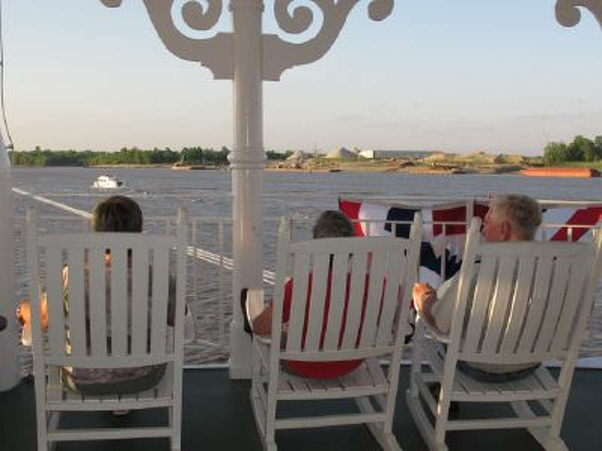 In this April 27, 2012 photo, passengers on the American Queen steamboat take in the view as they sit on rocking chairs as the vessel moves up the Mississippi River in Memphis, Tenn. The American Queen is the largest steamboat in the world, carrying 436 passengers. The 418-foot-long vessel is taking tourists on long-distance trips on the Mississippi for the first time since 2008, when its previous owner ceased operations.