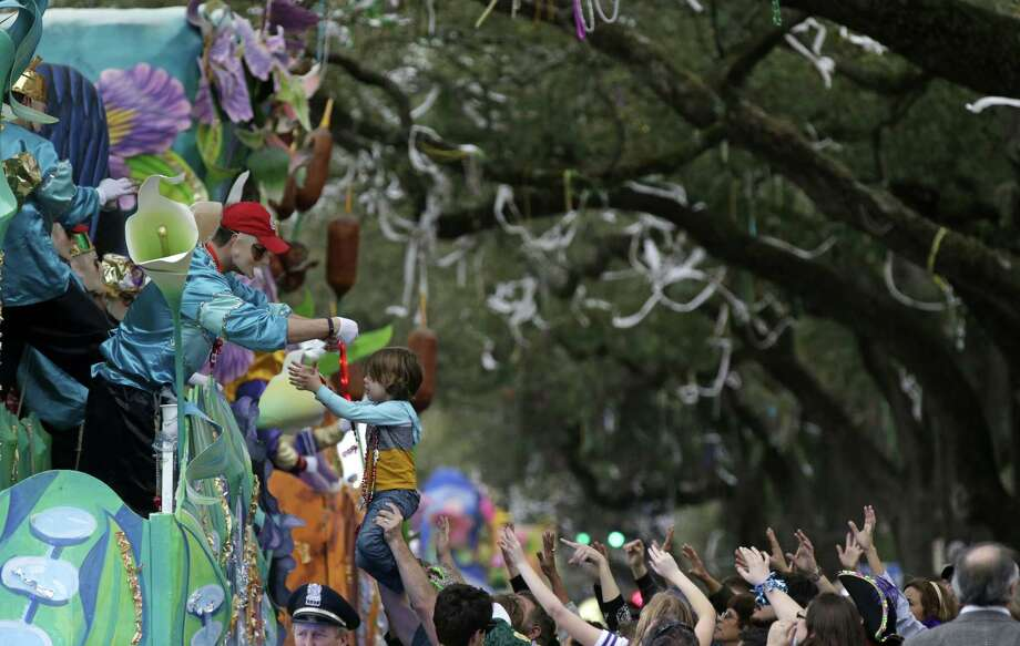 A float rider puts beads around the neck of a child during Krewe of Proteus Mardi Gras parade Monday in New Orleans. The day is known as Lundi Gras, the day before Mardi Gras. Photo: (AP Photo/Gerald Herbert) / AP