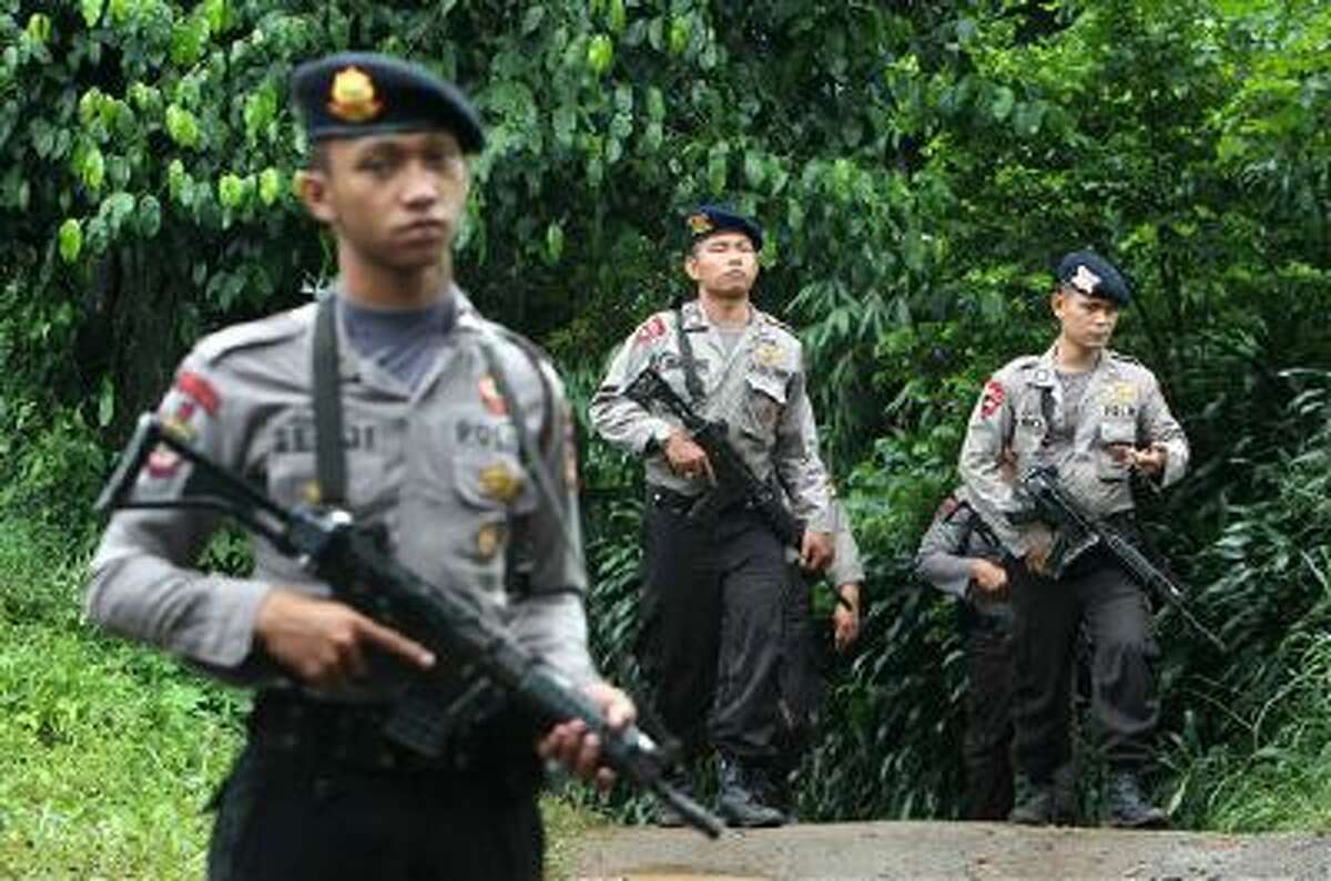 Police officers patrol the area near a house Wednesday that was used as a hideout by suspected militants following an overnight raid in Ciputat, Indonesia. Indonesia's elite anti-terrorism squad shot and killed six suspected militants amid New Year's Eve celebrations.