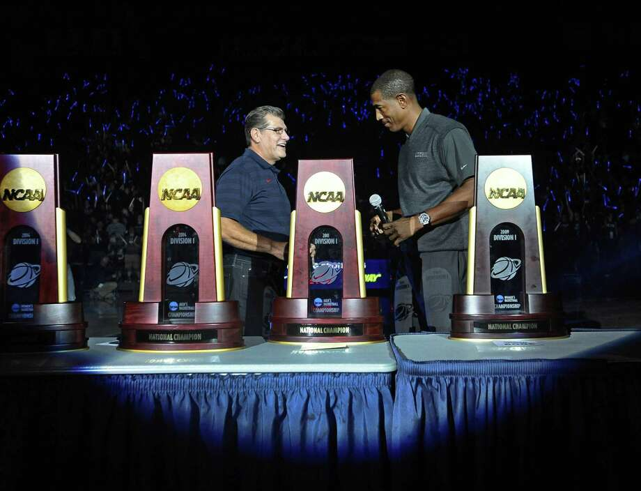 UConn women's basketball coach Geno Auriemma, left, and men's coach Kevin Ollie stand with the 13 national championship trophies won by the two programs since 1995 during the Huskies' First Night festivities on Friday in Storrs. Photo: Jessica Hill — The Associated Press  / FR125654 AP
