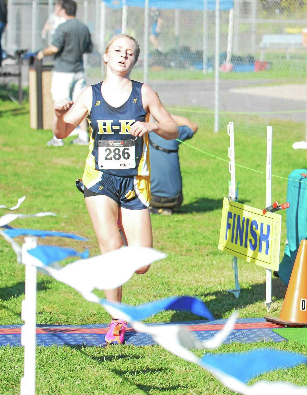 Haddam-Killingworth junior Maddie Brandon crosses the finish line after winning her second straight Shoreline Conference championship Friday at Old Saybrook.