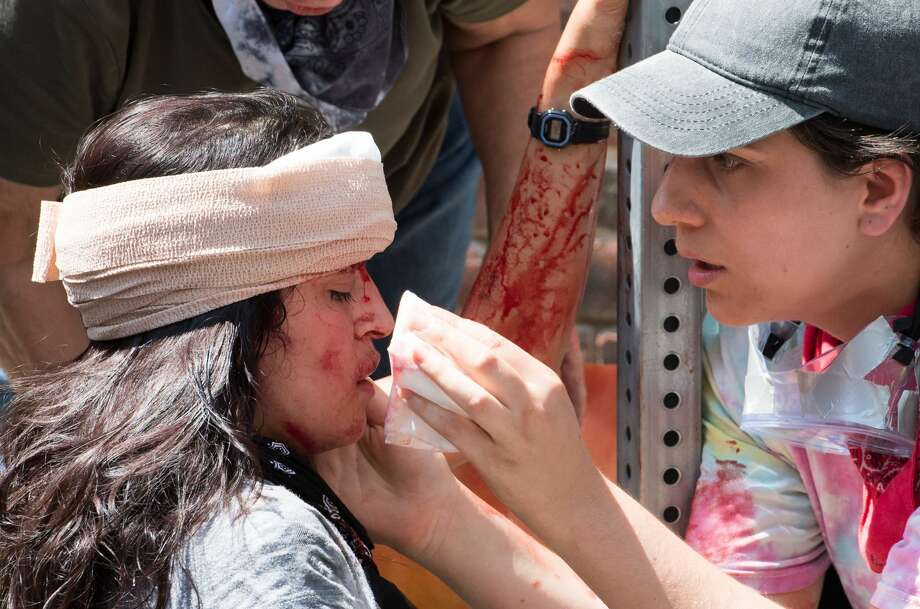 A woman, later identified as 20-year-old University of Virginia student Natalie Romero, receives first aid after a car plowed into a crowd of counterprotesters Saturday in Charlottesville, Virginia. Photo: PAUL J. RICHARDS/AFP/Getty Images