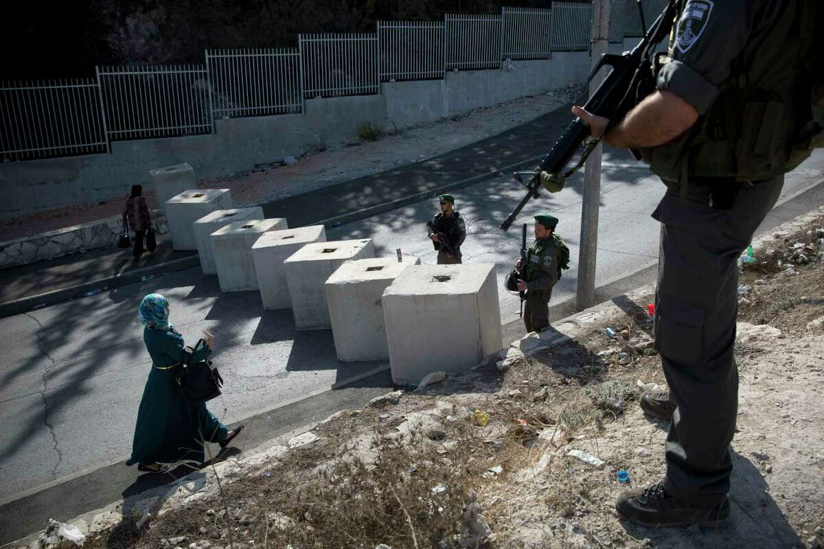 Israeli border police check the ID of a Palestinian woman, next to newly placed concrete blocks in an east Jerusalem neighborhood, Thursday, Oct. 15, 2015. Israel erected checkpoints and deployed several hundred soldiers in the Palestinian areas of the city Wednesday as it stepped up security following a series of attacks in Jerusalem.