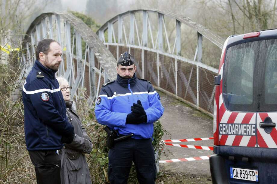 Police officers guard the entrance of the Jewish cemetery in Sarre-Union, eastern France, where hundreds of graves have been vandalized, Monday, Feb. 16, 2015. Hundreds of Jewish tombstones were found vandalized in eastern France on Sunday, hours after a Danish Jew guarding a synagogue in Copenhagen was shot to death. Investigators were questioning five minors, 15 to 17 years old, in connection with the vandalized cemetery, the prosecutor of the eastern Bas-Rhin region told a news conference. One of the five had turned himself in. (AP Photo/Christian Lutz) Photo: AP / AP