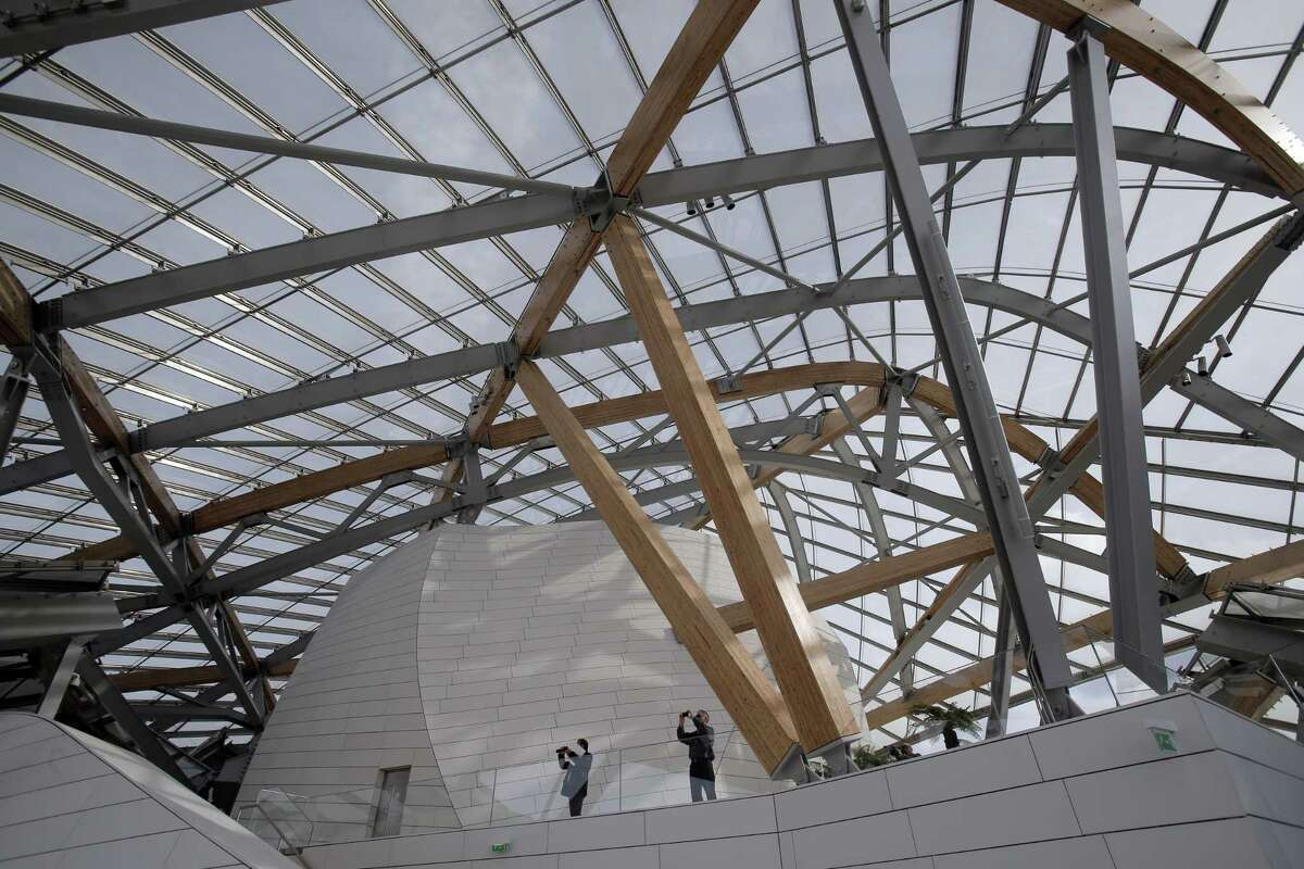 Members of the media take photographs inside the Louis Vuitton Foundation art museum and cultural center, created by American architect Frank Gehry, during the press day, in Paris, Friday Oct. 17, 2014. The 100-million-euro building, with billowing glass casing and 11 gallery spaces, has been compared to an iceberg or giant sailboat and took over a decade to make.