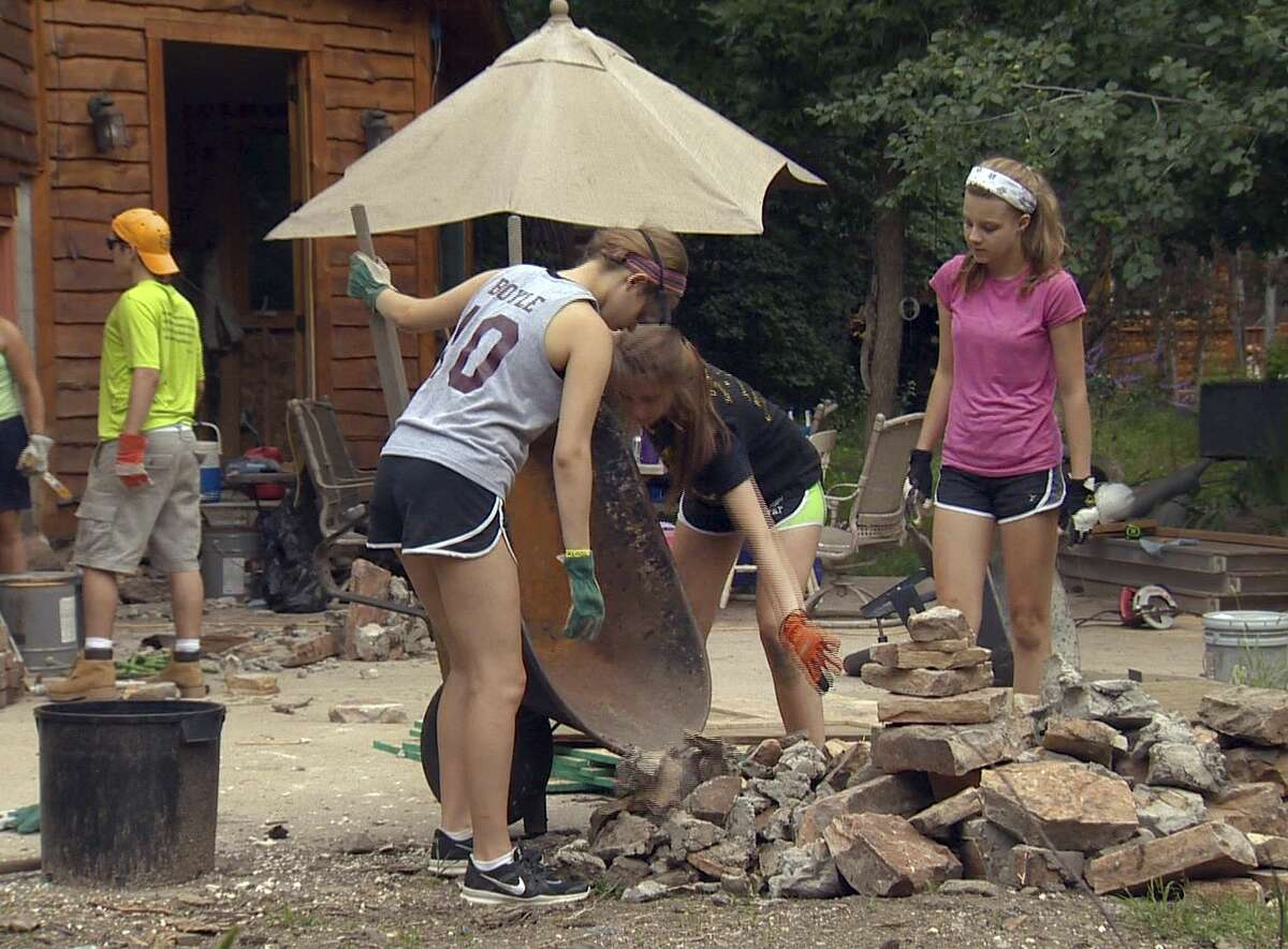 In this July 31, 2014 photo released by Ben's Lighthouse, Clare Boyle, left, Kate Fallon, center, and Rachel Wolf, right, move stones during the group's service project in Loveland, Colo. The annual service trip is run by Benís Lighthouse, a nonprofit founded to help children from Newtown, Conn., recover from the December 2012 massacre at Sandy Hook Elementary School. The organization is named after 6-year-old victim Ben Wheeler. The third annual trip will be in July 2015 to Colorado help rebuild homes devastated in the previous yearís flooding. (Ben's Lighthouse/Sue Vogelman via AP)
