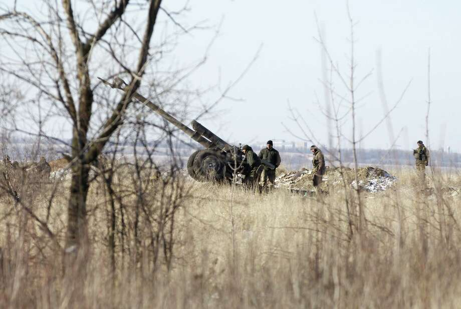 Ukrainian artillery is at a position outside of the village of Luhanske, some 20 kilometers (14 miles) north of Debaltseve, Ukraine, Tuesday, Feb. 17, 2015. Ukrainian government troops and Russia-backed rebels failed Tuesday to start pulling back heavy weaponry from the front line in eastern Ukraine as a deadline passed to do so. Under a cease-fire agreement negotiated by the leaders of Ukraine, Russia, Germany and France last week, the warring sides were to begin withdrawing heavy weapons from the front line on Tuesday. (AP Photo/Petr David Josek) Photo: AP / AP