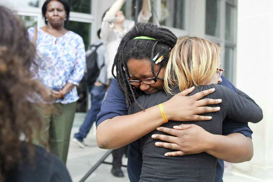 Jacquis Roberston, left, embraces her friend Laura Sprague moments after a vigil to mourn the lives lost at the shooting in Charleston, S.C., June 18, in Kalamazoo, Mich. Dylann Storm Roof, 21, was arrested Thursday in the slayings of several people, including the pastor at a prayer meeting inside a historic black church. Photo: Daytona Niles — Kalamazoo Gazette Via AP   / The Kalamazoo Gazette