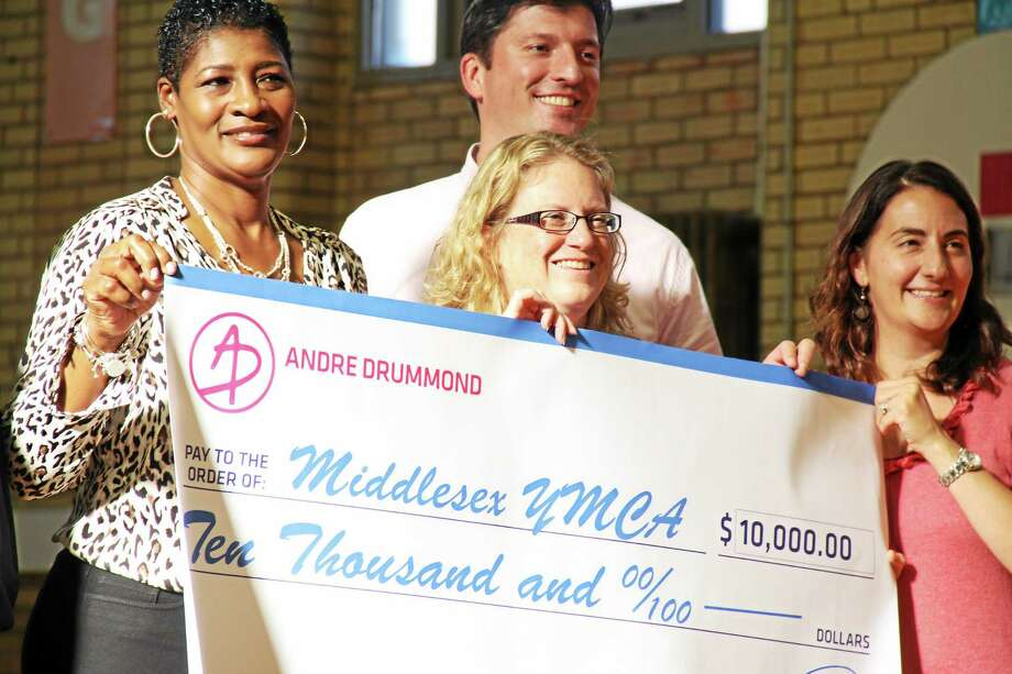 From left, Detroit Pistons player Andrew Drummond's mother Christine Cameron presents a $10,000 donation to Michele Rulnick, the president of the Northern Middlesex County YMCA in Middletown, alongside Robert Mosca, Director of Major Gifts at Wesleyan University, and deputy city attorney Kori Termine Wisneski, a YMCA board member. Photo: Kathleen Schassler — Middletown Press  / Kathleen Schassler All Rights
