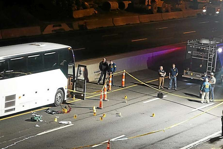 Law enforcement investigate the scene of a stabbing aboard a tour bus late Tuesday, Oct. 14, 2014 in Norwalk, Conn. A man who stabbed passengers on the casino-bound tour bus on Interstate 95 was fatally shot by state police, officials said. Photo: AP Photo/The Hour, Jeff Dale  / The Hour