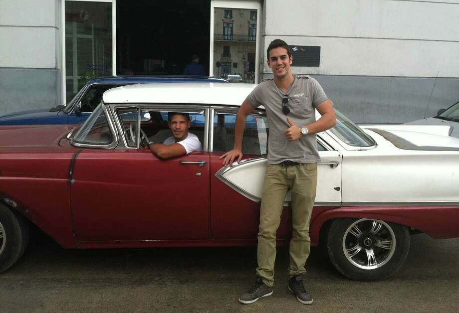 Mario Otero in front of a classic American car driven by his friend Camilo Rodriguez in Havana, Cuba. Otero, 25, works as a waiter in one of Havana's best restaurants, has a tourism degree, moonlights as a private tour guide with a goal of someday opening his own tourism agency, and sees increased tourism in Cuba as a key to achieving his dreams. Photo: Beth J. Harpaz — The Associated Press  / AP