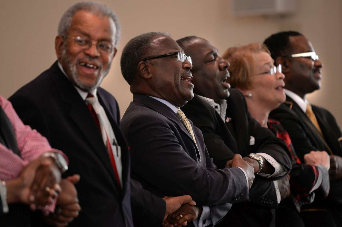 """Ministers, including Mount Moriah Pastor Dr. Benjamin Snoddy, center, hold hands during the singing of """"We Shall Overcome"""" during a service at the Mount Moriah Baptist Church in Spartanburg, S.C. on Saturday, June 20, 2015, in honor of those shot and killed in a Charleston, S.C. church earlier in the week."""