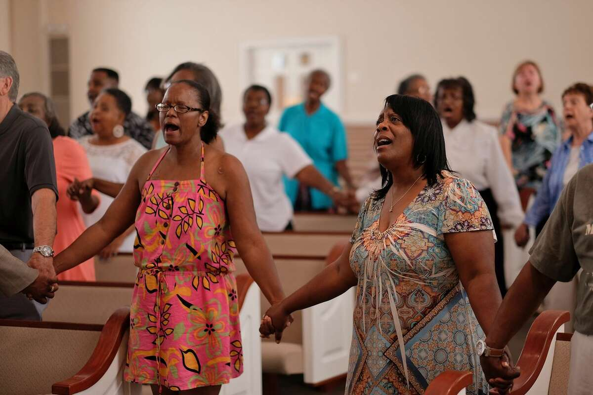 Worshippers hold hands during a service at the Mount Moriah Baptist Church in Spartanburg, S.C. on Saturday, June 20, 2015, in honor of those shot and killed in a Charleston, S.C. church earlier in the week.