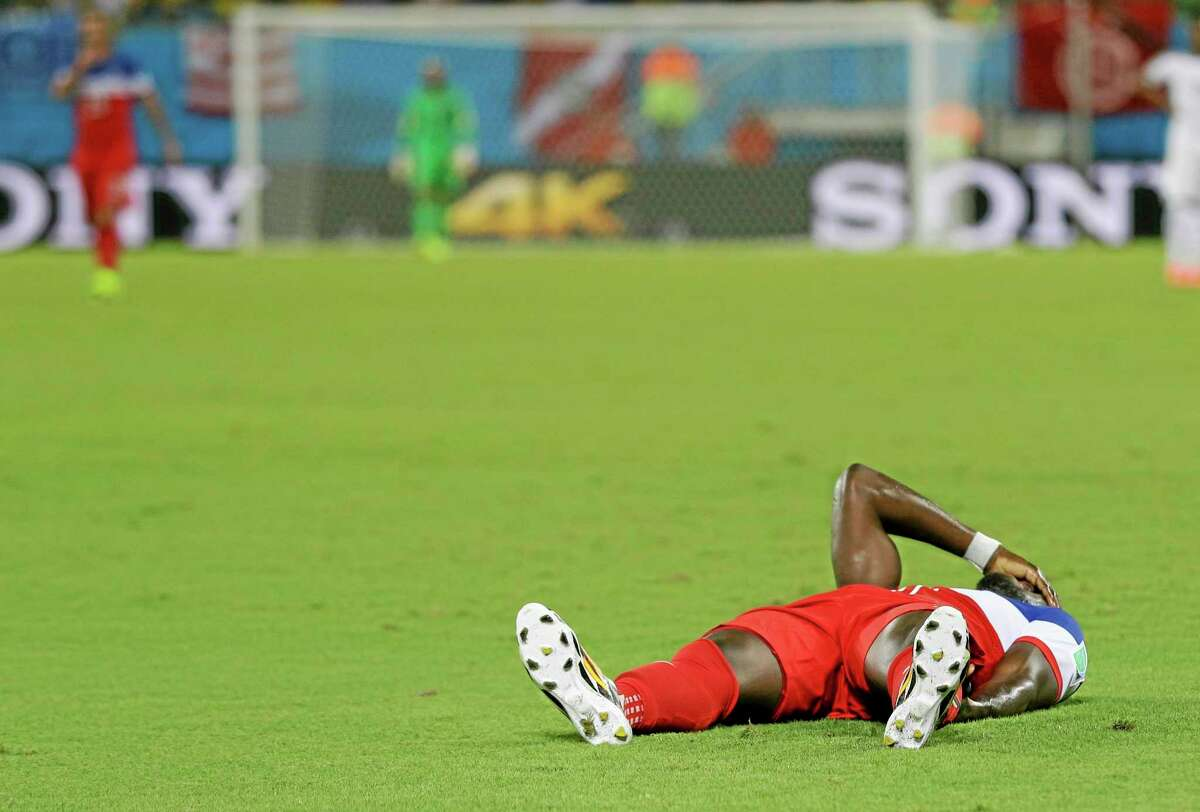 Jozy Altidore holds his hand to his face as he lies on the pitch after pulling up injured during the group G World Cup soccer match between Ghana and the United States on Monday at the Arena das Dunas in Natal, Brazil.