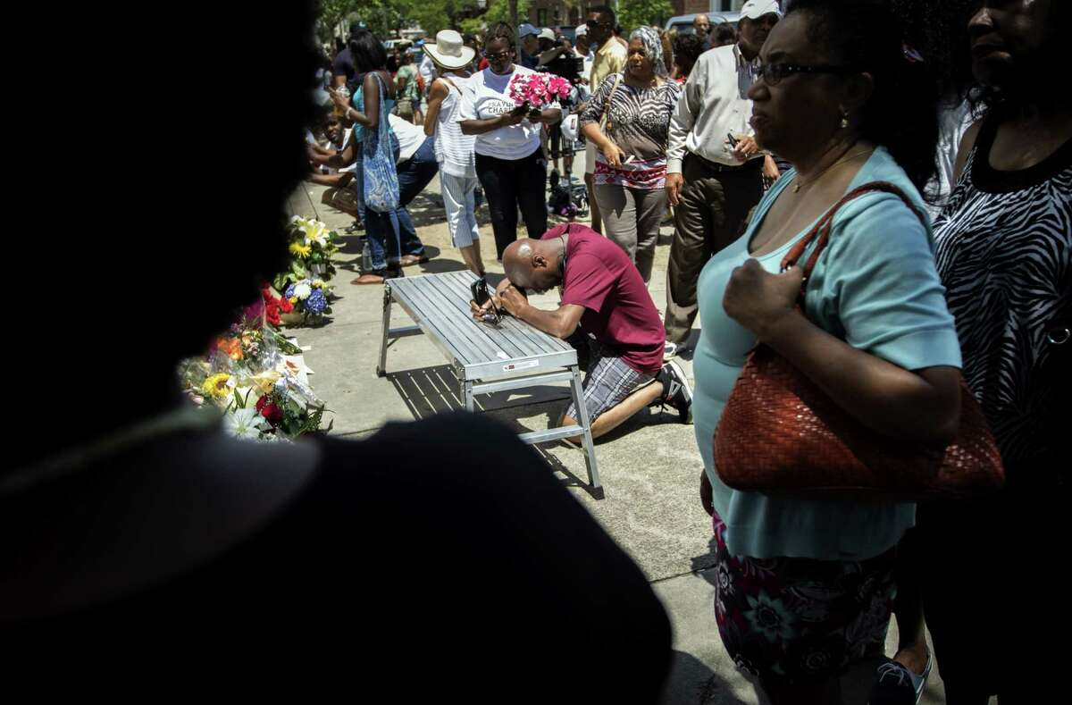 A man kneels in prayer as people around him lay flowers and messages of hope and faith at the memorial outside the Emanuel AME Church, Saturday, June 20, 2015, in Charleston, S.C. A constant stream of people have visited the site where nine people where killed by a gunman while attending bible study. (AP Photo/Stephen B. Morton)