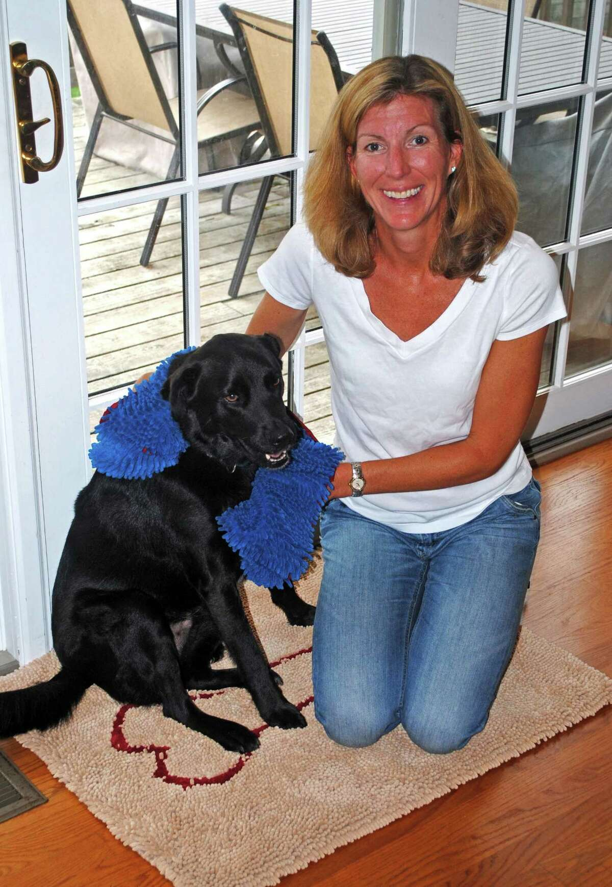 Joanna Rein, of Larchmont, N.Y., poses at her home with her Labrador-collie named Buddy. Because Buddy was always tracking mud or water into the house, Rein created Soggy Doggy, a doormat that absorbs most of the mess on the mutt.