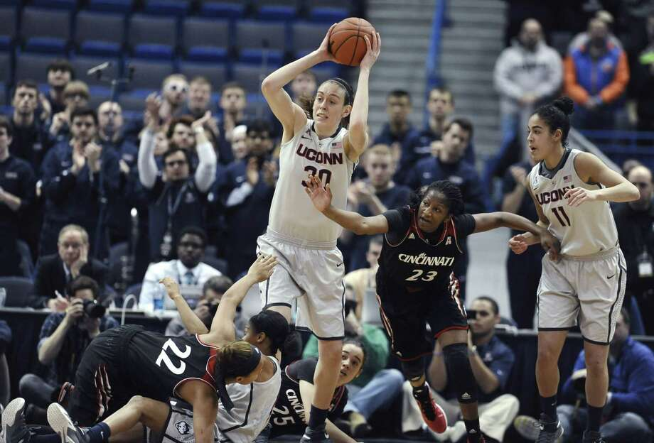 Connecticutís Breanna Stewart (30), grabs a loose ball against Cincinnatiís Jasmine Whitfield (23) as Kia Nurse (11), right, watches and Cincinnatiís Bianca Quisenberry (22) and Connecticut's Moriah Jefferson tumble to the court, during the first half of an NCAA college basketball game, Tuesday, Feb. 3, 2015, in Hartford, Conn.  (AP Photo/Jessica Hill) Photo: AP / FR125654 AP