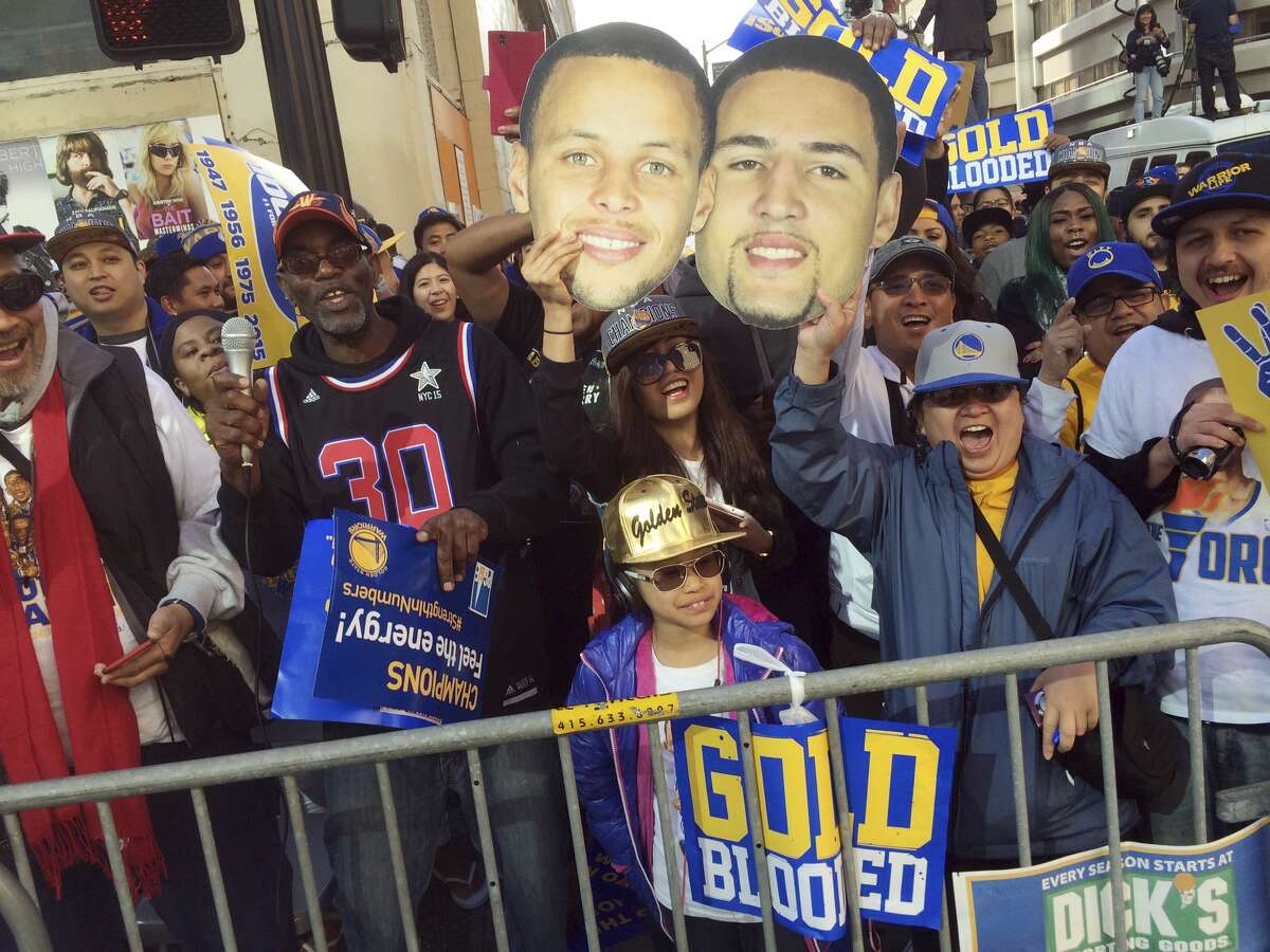 Golden State Warriors fans cheer from the sidewalk holding pictures of players Stephen Curry, left, and Klay Thompson as they wait for the start of the team's world championship parade on Friday in Oakland, Calif.