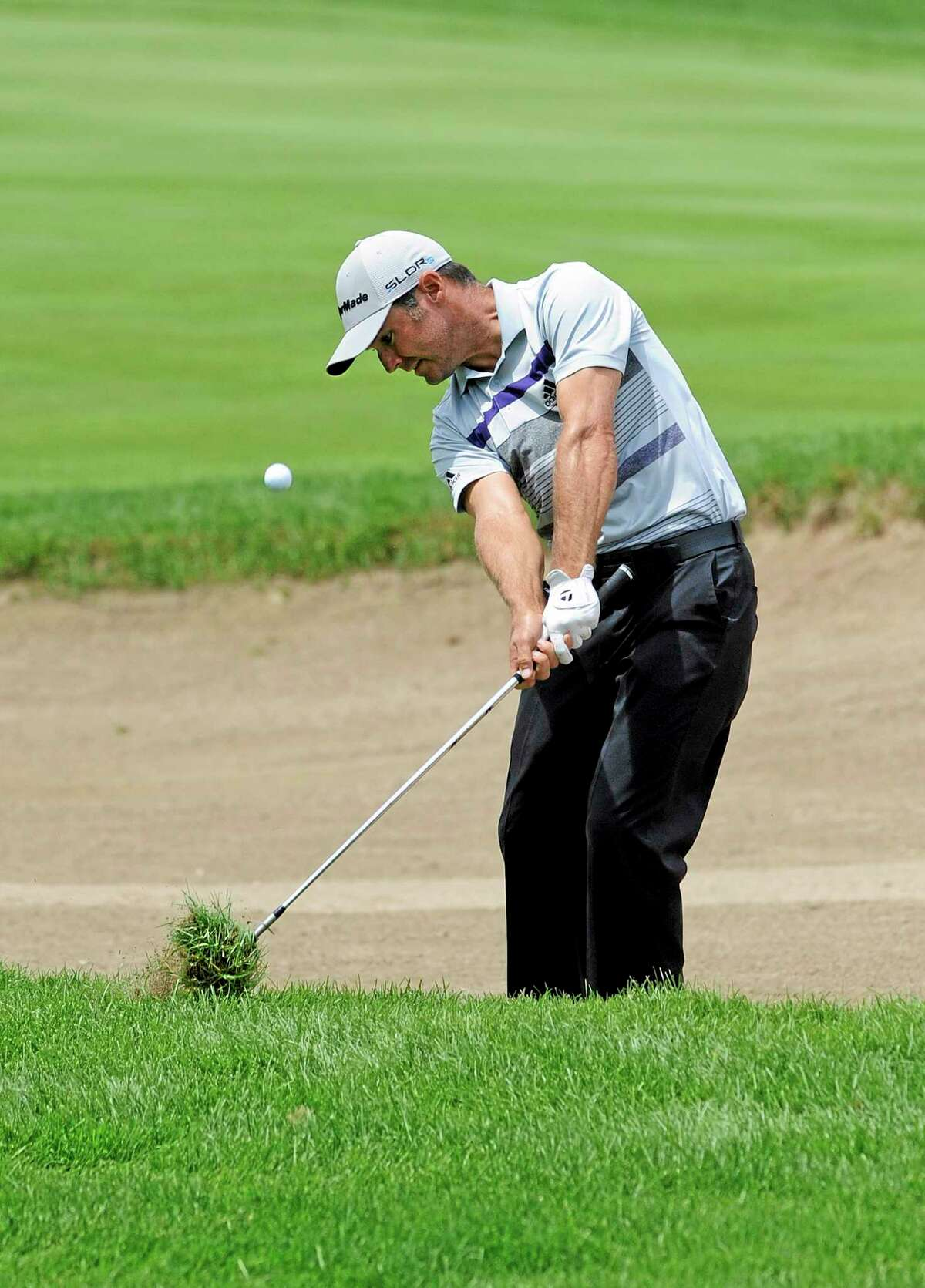 Trevor Immelman, here hitting out of the rough on the 9th hole, made double-eagle on the par-5 13th hole during the first round of the Travelers Championship Thursday in Cromwell.