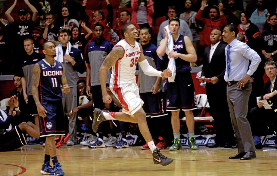 Houston's TaShawn Thomas (35) celebrates at the final buzzer, between Connecticut coach Kevin Ollie, right, and guard Ryan Boatright (11), at an NCAA college basketball game Tuesday, Dec. 31, 2013, in Houston. Houston defeated Connecticut 75-71. (AP Photo/Bob Levey) Photo: AP / FR156786 AP