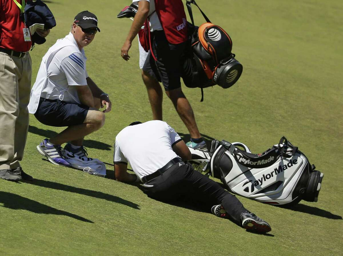 Jason Day lies in the fairway after falling down as his caddie, Colin Swatton, crouches beside him on the ninth hole during the second round of the U.S. Open Friday at Chambers Bay in University Place, Wash.