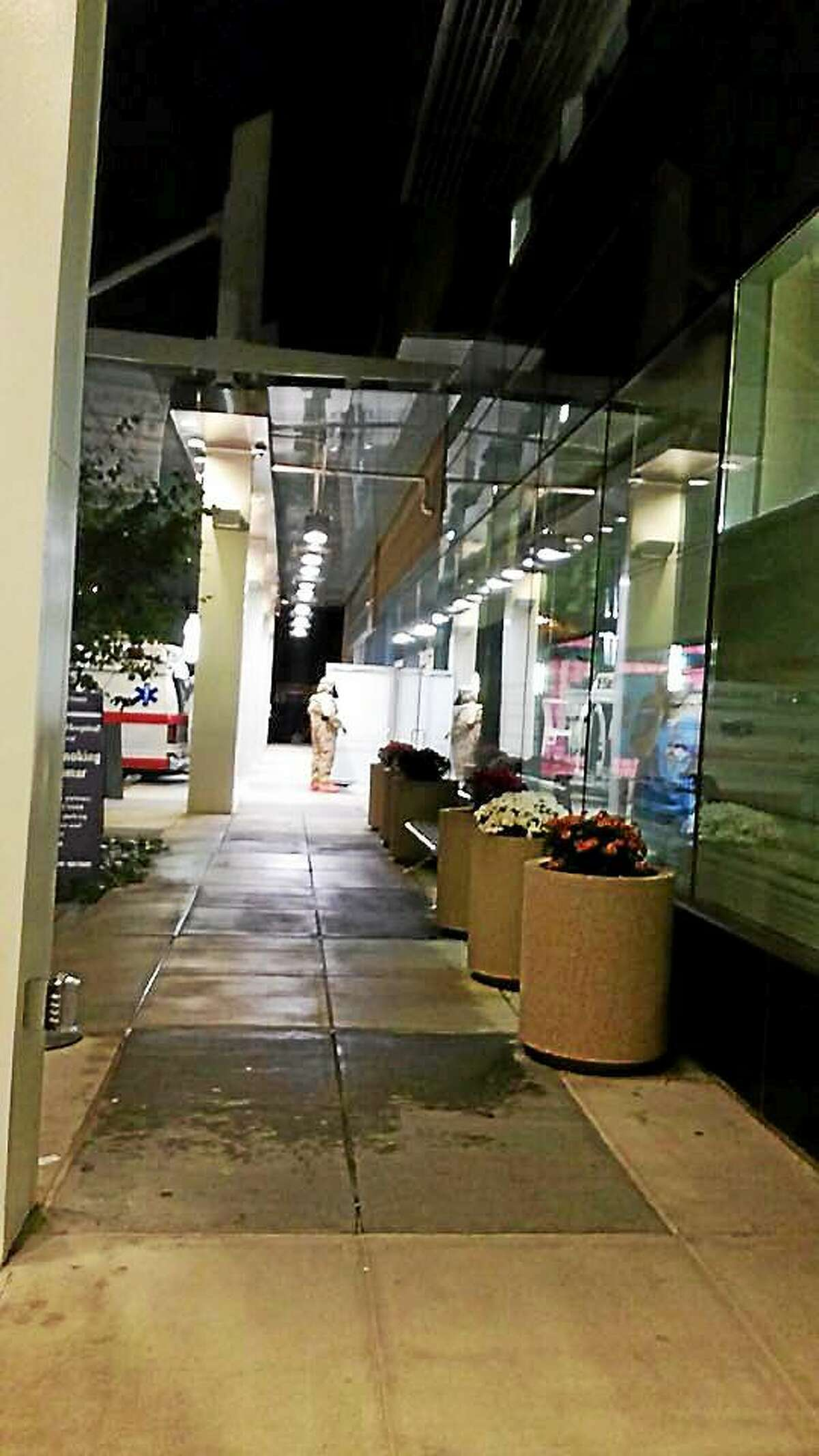A worker in protective gear can be seen outside Yale-New Haven Hospital Wednesday night. Hospital officials confirmed Thursday a patient with Ebola-like symptoms was being treated there. Photo from Amy Giannotti