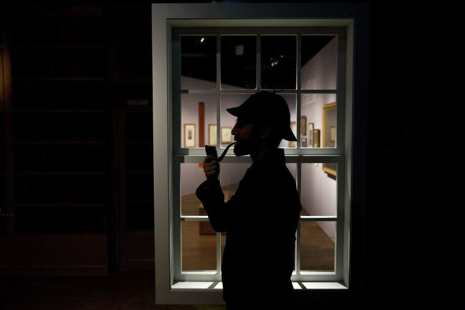 "Curator Timothy Long is silhouetted as he poses for photographers with a Sherlock Holmes style pipe and deerstalker hat beside an internal window forming part of the exhibition ""Sherlock Holmes:  The Man Who Never Lived and Will Never Die"" at the Museum of London in London, Thursday, Oct. 16, 2014. The exhibition, which opens to the public on Friday, is the largest on the fictional detective created by Scottish author Sir Arthur Conan Doyle to be held in the UK for 60 years  (AP Photo/Matt Dunham) Photo: AP / AP"